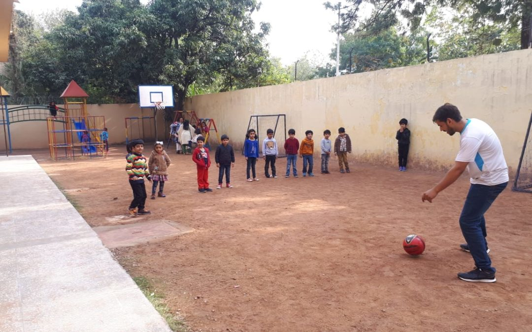 Pre-schoolers playing football